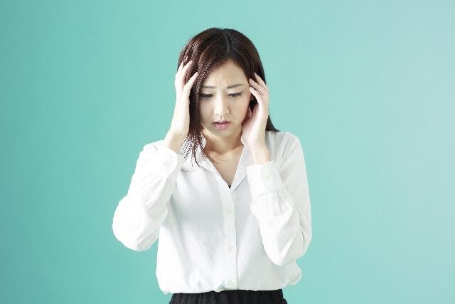 頭を抱える女性のイメージ画像